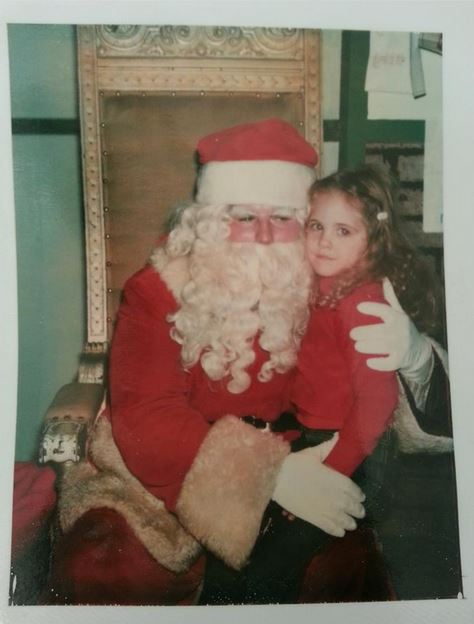 """A rare Christmas visiting Santa and Mrs. Claus at my dad's work where I didn't """"take one for the team"""" and settle for a visit with Mrs. Claus instead, because her line was shorter than Santa's line. I actually saw Santa himself! The look on my face reads: I'm uncomfortable."""