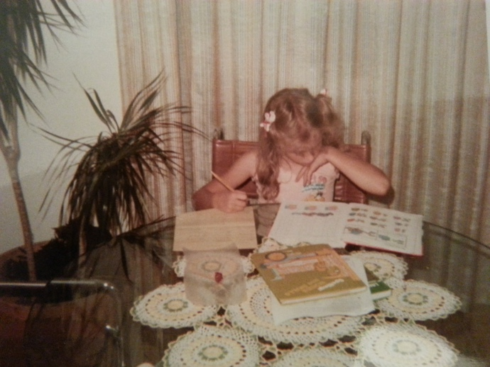 Me doing third grade homework at the kitchen table in front of the potted palm. Still valiantly hanging onto its leaves in 1984.