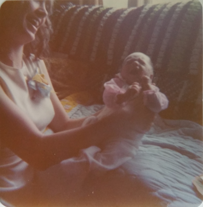 Mom and Me on our very first Mother's Day when I was a month old! Even as I'm wailing the joy on Mom's face as she holds me is worth a thousand words. Or rather, it epitomizes one word: Mom.